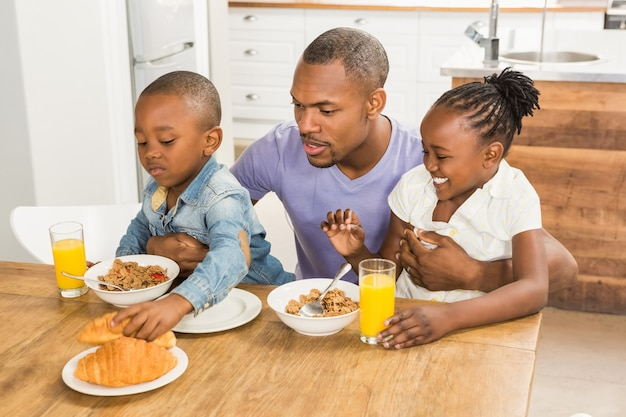キッチンで朝食をするカジュアルな幸せな家族