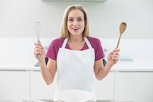 Casual laughing blonde showing wooden spoon and whisk