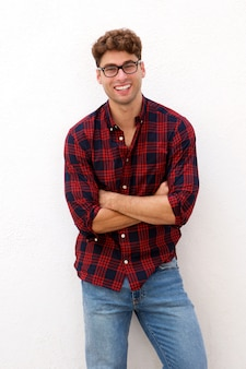 Casual laughing man with glasses standing with arms crossed