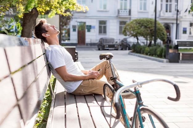 屋外で音楽を聴くカジュアルな男性