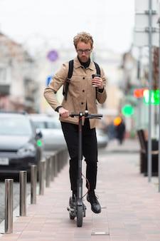 Maschio casuale in posa con uno scooter elettrico