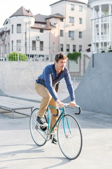 Casual male riding bicycle outdoors
