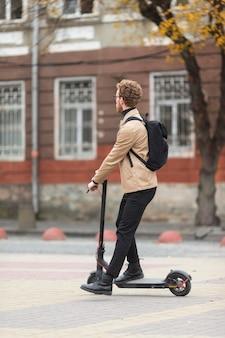 Maschio casuale in sella a uno scooter elettrico