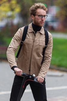 彼の電動スクーターに乗ってカジュアルな男性