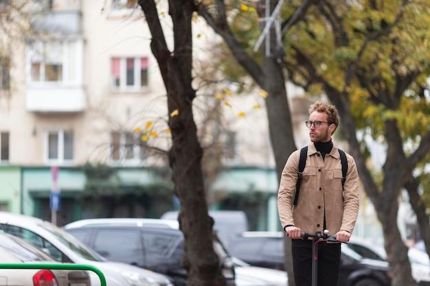 屋外でスクーターに乗るカジュアルな男性