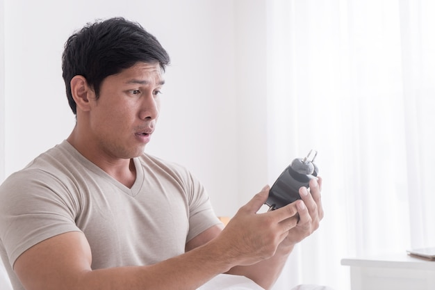 Casual man is surprise on late alarm clock time