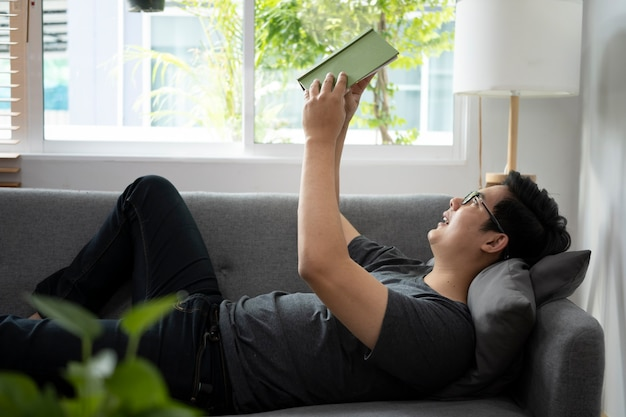 Случайный человек лежал на удобном диване и читал книгу.