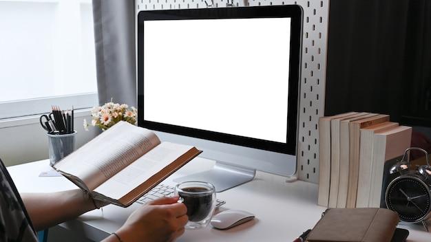Случайный человек читает книгу и пьет кофе в домашнем офисе.