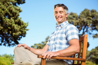 Casual man relaxing on park bench