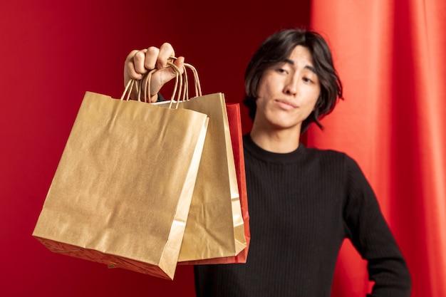 중국 새 해에 대 한 종이 쇼핑백을 보여주는 캐주얼 남자