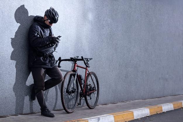 カジュアルな男が自転車で灰色のコンクリートの壁の近くに立って、電話を見ています。都会的なスタイル。