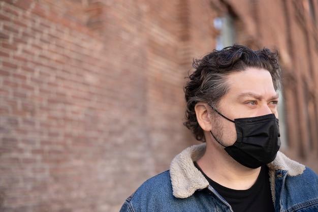 Случайный мужчина с голубыми глазами и медицинской маской на кирпичной стене