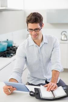 キッチンにデジタルタブレットと日記を持つカジュアルマン