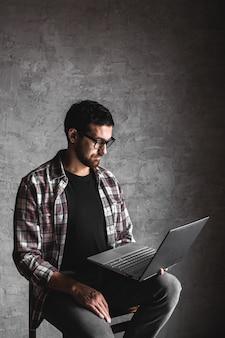 Случайный человек с ноутбуком на сером фоне. интернет, образование, работа, досуг