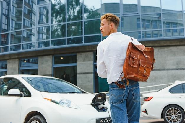 배터리 충전 과정이 끝나기를 기다리는 전기차 근처에 스마트폰을 들고 있는 캐주얼 남자