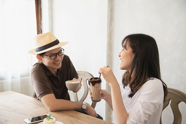 Casual man and woman talking happily while drink coffee