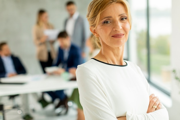 그녀의 팀 앞에 사무실에 서있는 캐주얼 성숙한 비즈니스 우먼