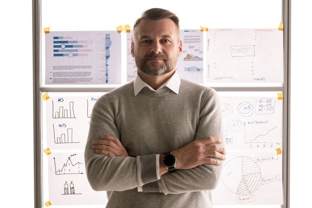 Casual mature businessman crossing arms by chest while standing against whiteboard with documents