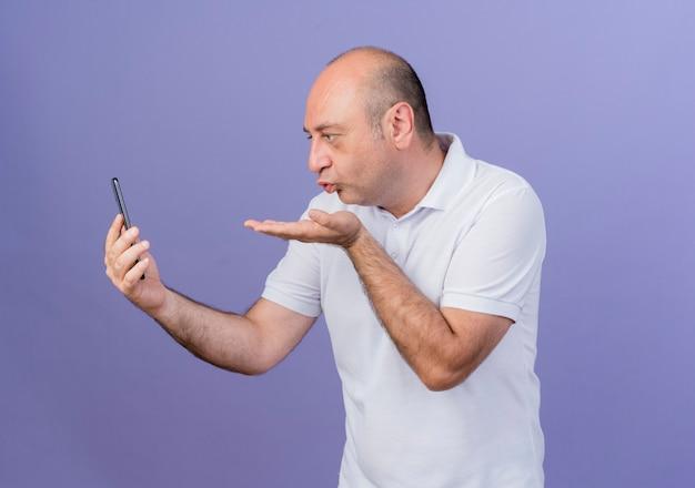 携帯電話を保持し、見て、紫色の背景で隔離のブローキスを送信するカジュアルな成熟したビジネスマン