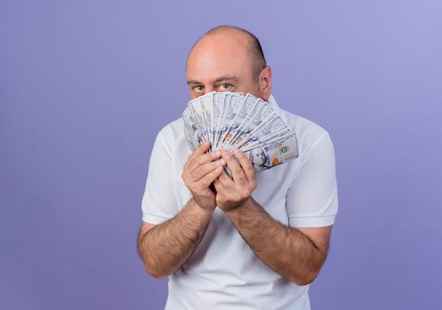 돈을 들고와 복사 공간 보라색 배경에 고립 된 돈 뒤에서 카메라를 찾고 캐주얼 성숙한 사업가
