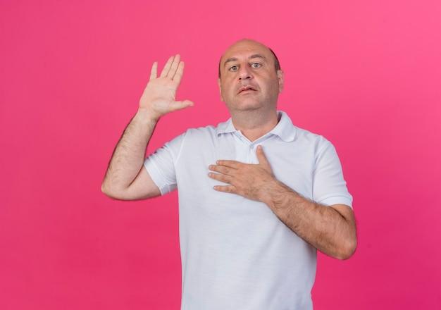 カメラを見て、コピースペースでピンクの背景に分離された約束ジェスチャーを行うカジュアルな成熟したビジネスマン
