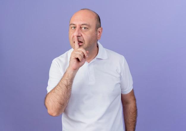 Случайный зрелый бизнесмен смотрит в камеру и делает жест молчания, изолированный на фиолетовом фоне с копией пространства