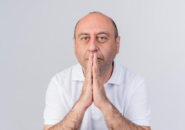 Случайные зрелые бизнесмен, глядя в камеру, держа руки вместе в жесте молитвы на губах, изолированные на белом фоне