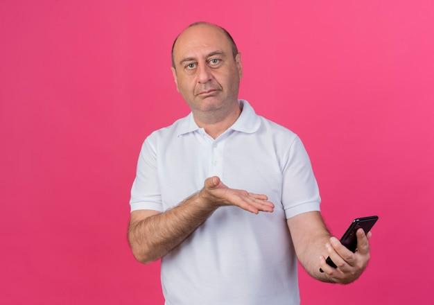 Casual uomo d'affari maturo guardando davanti tenendo e indicando con la mano al telefono cellulare