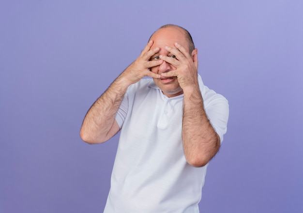 캐주얼 성숙한 사업가 얼굴에 손을 넣고 복사 공간이 보라색 배경에 고립 된 손가락을 통해 카메라를보고