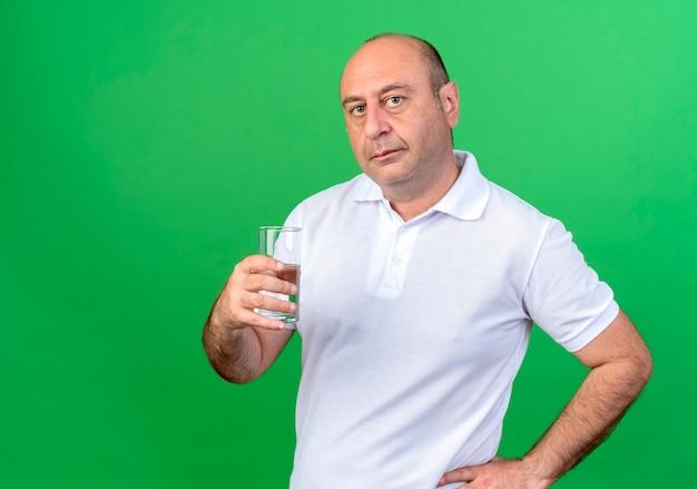 カジュアルな成熟した男は、水のガラスを保持し、コピースペースと緑の壁に分離された腰に手を保持します。