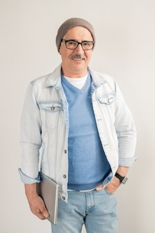 ブルージーンズとプルオーバー、白いジャケット、眼鏡、白い壁にビーニー立っているカジュアルな成熟した男