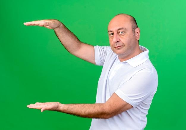 コピースペースで緑に分離されたサイズを示すカジュアルな成熟した男