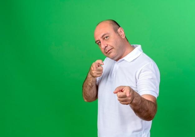 녹색 벽에 고립 된 제스처를 보여주는 캐주얼 성숙한 남자