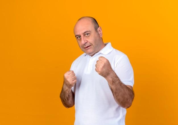 노란색 벽에 고립 된 포즈 싸움에 서있는 캐주얼 성숙한 남자