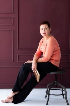 スツールに座っているカジュアルな成熟した女性