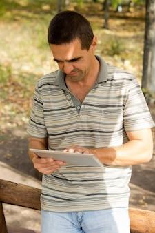 그가 그의 손에 들고있는 터치 스크린 태블릿에 캐주얼 중년 남자 서 타이핑