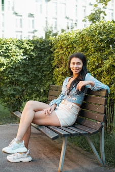 Casual outfit woman sitting on a bench