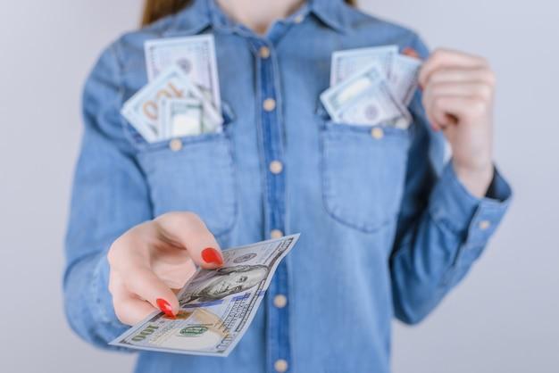 캐주얼 사람 라이프 스타일 새로운 홀드 럭셔리 행복 행복 부 보너스 상금 수상 개념. 회색 배경에 격리된 돈을 주는 예쁜 여성의 손을 클로즈업한 초상화