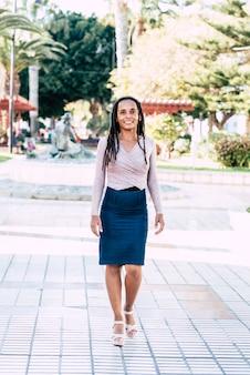 街の背景で屋外を歩き、カメラに微笑んでいるドレッドヘアの髪を持つ若い黒人女性のカジュアルな肖像画-立って移動している現代の代替の人々