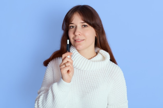 Casual pretty woman standing and vaping over blue while looking directly at camera, girl with dark hair dresses white jumper, holds e cigarette.
