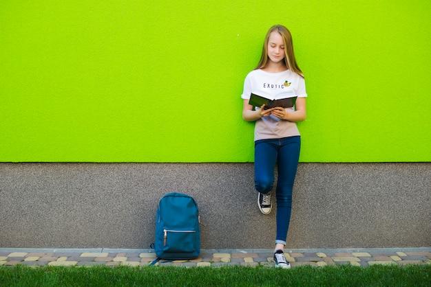 Casual schoolgirl reading book outside of university