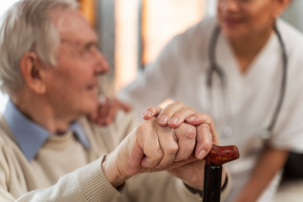 Casual senior man at home with doctor