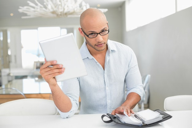 Случайный серьезный человек с цифровым планшетом и дневником у себя дома