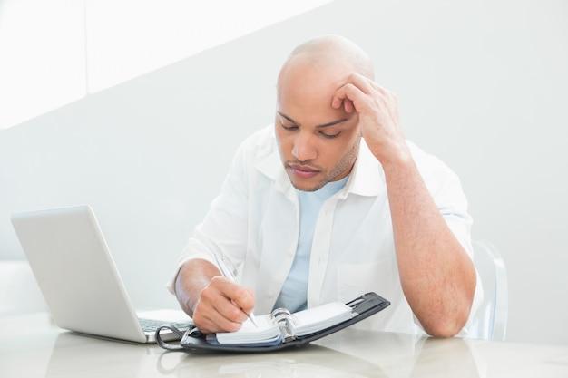 Случайный серьезный человек с записью ноутбука в дневник
