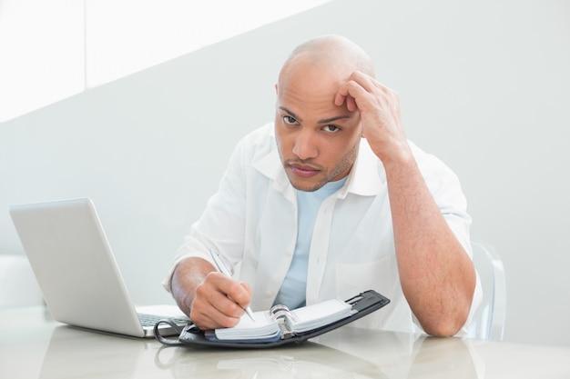 Случайный серьезный человек с записью ноутбука в дневник Premium Фотографии