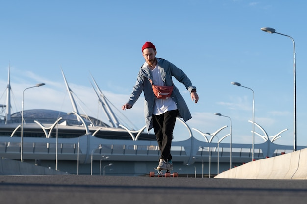 Casual skater man on longboard at urban space hipster man wearing trendy street fashion clothes