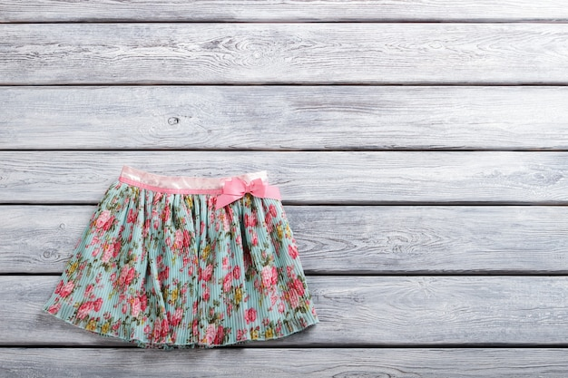 Casual skirt with floral print skirt on gray wooden background new clothing item on sale last size a...