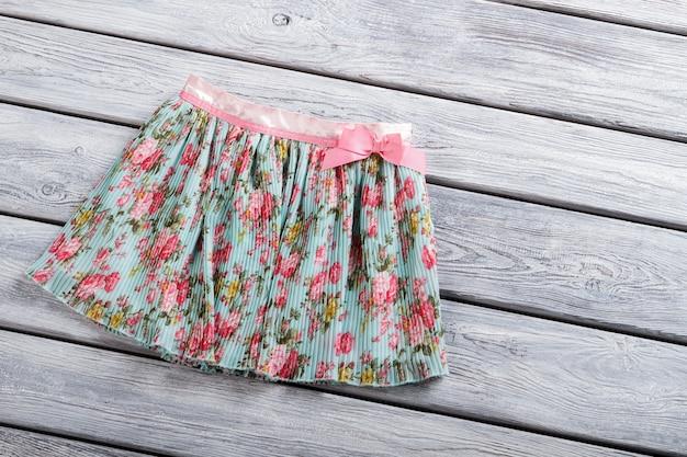 플라워 프린트의 캐주얼 스커트. 나무 배경에 짧은 치마. 선반에 다채로운 의류 항목입니다. 패션 매장에서 판매되는 의류.