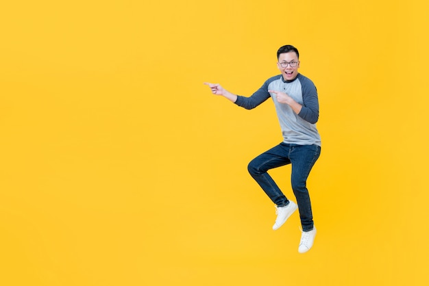 Casual smiling asian man jumping and pointing fingers to copy space aside