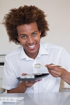 彼の机で寿司を食べるカジュアルな笑顔のビジネスマン